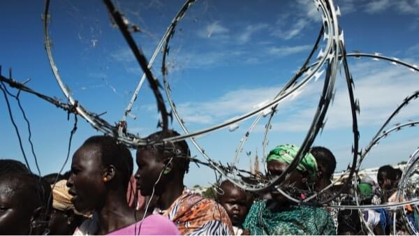 Queue beside a barbed wire fence surrounding an UN protection of civilians camp near Juba