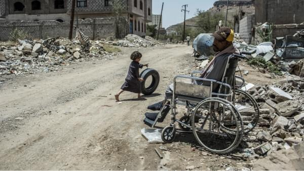A young boy passes a man in a wheelchair as he plays with a car tyre in Sana'a, which has been devastated by attacks on civilians
