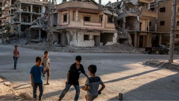 Un groupe de jeunes garçons jouent au football pendant le ramadan dans des rues bordées de bâtiments détruits à Raqqa