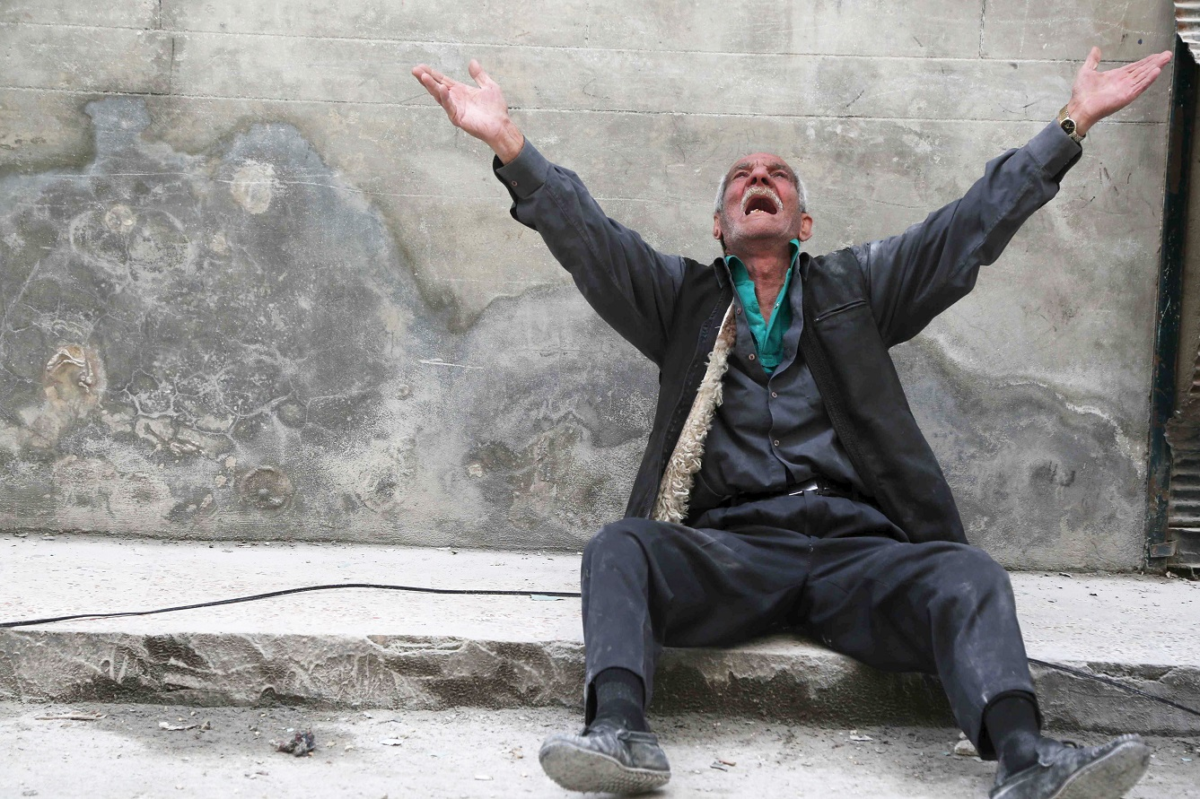 A man reacts at a site hit by what activists say was a barrel bomb dropped by forces loyal to Syria's President Bashar al-Assad, in Aleppo's al-Fardous district April 29, 2015. REUTERS/Hosam Katan - RTX1ASFQ