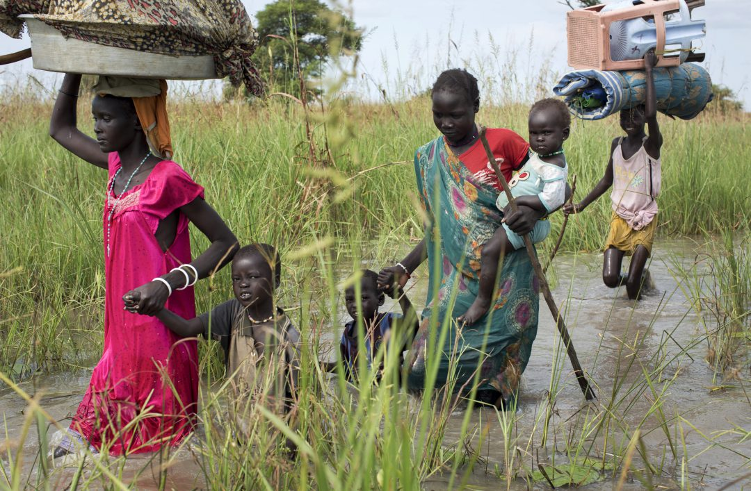A family from the Nuer rebel-controlled area, walk through flooded areas to reach a makeshift camp in the United Nations Mission in South Sudan (AP Photo/Matthew Abbott)